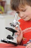 Pojke med mikroskopet Fotografering för Bildbyråer