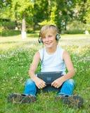 Pojke med minnestavlan och hörlurar Arkivfoton