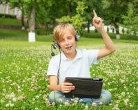 Pojke med minnestavlan och hörlurar Arkivbilder