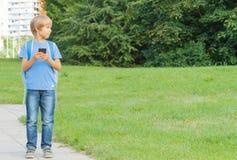 Pojke med mobiltelefonen i gatan genom att använda modiga apps och se omkring gata för bakgrundsstadsnatt Skola teknologi, fritid Royaltyfria Bilder
