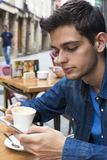 Pojke med mobiltelefonen på terrassen Arkivbild