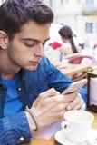 Pojke med mobiltelefonen på terrassen Fotografering för Bildbyråer