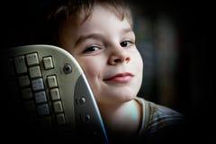 Pojke med PCtangentbordet Fotografering för Bildbyråer