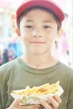 Pojke med pommes frites arkivfoton
