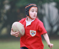 Pojke med röd omslagsspelrumrugby Royaltyfri Foto