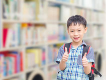Pojke med ryggsäcken i skola Arkivbild