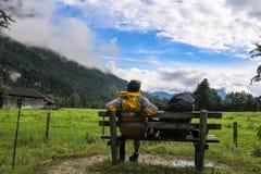 Pojke med ryggsäcksammanträde på bänk i mitt av fjällängar för bergbavarianTyskland framme av härlig grön fältsiktsdimma på Royaltyfri Fotografi