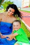 Pojke med sammanträde och att skratta för moder Håll handen för mamma` s Arkivbild