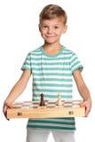 Pojke med schackbrädet Royaltyfria Foton