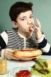 Pojke med själven som göras den enorma hotdogen att le Royaltyfri Bild