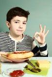 Pojke med själven som göras den enorma hotdogen att le Royaltyfri Foto