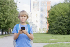 Pojke med smartphonen i gatan Barn som använder apps, spelar, skriver eller läser meddelandet gata för bakgrundsstadsnatt skola Arkivfoto