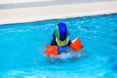 Pojke med solskyddskläder som spelar i barnens pöl Fotografering för Bildbyråer