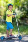 Pojke med sparkcykeln i parkera Arkivfoto