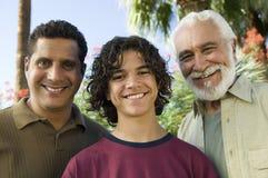 Pojke (13-15) med ståenden för främre sikt för fader och för farfar utomhus. royaltyfri fotografi