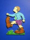 Pojke med stora skor, träskulptur Arkivfoton