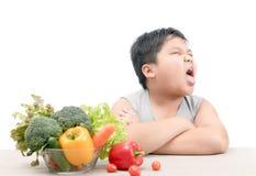 Pojke med uttryck av avsmak mot grönsaker royaltyfri fotografi