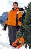 Pojke med vinterkläder och snöskor Arkivfoton