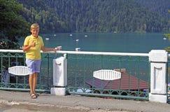 Pojke mot bakgrunden av sjön Ritsa fotografering för bildbyråer