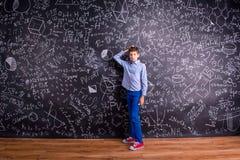 Pojke mot den stora svart tavla med matematiska symboler och formel Royaltyfria Bilder