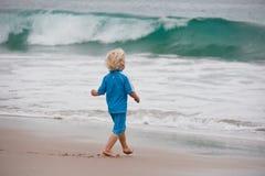 pojke in mot gå waves Royaltyfri Foto