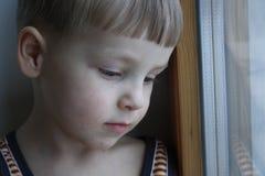 Pojke nära fönstret Arkivfoto
