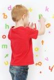 Pojke och alfabet Arkivfoto