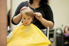 Pojke och att ha hårsnittet Royaltyfri Foto