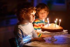 Pojke och broder för liten unge som blåser stearinljus på födelsedagkakan Fotografering för Bildbyråer