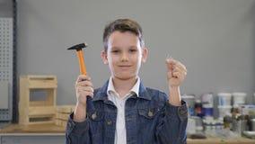 Pojke- och byggnadsverktyg med hammaren och spikar i händer som stänger och öppnar att le för ögon Handcraft begreppet hobby stock video