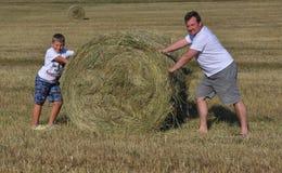 Pojke och fader med höstacken i ängen Arkivfoto