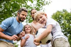 Pojke och familj med bollen arkivbilder