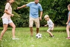 Pojke och familj som spelar fotboll royaltyfria bilder