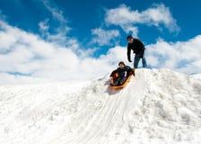 Pojke och farsa som sledding i vinter Arkivfoto