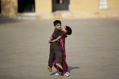 Pojke och flicka för redaktörs- foto som lycklig spelar i borggården av Amber Fort i Jaipur Royaltyfri Fotografi