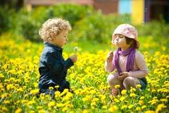 Pojke och flicka i blommor Arkivfoton
