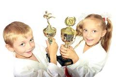 Pojke och flicka i en kimono med en mästerskap som segrar i händerna av Royaltyfri Fotografi