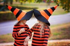 Pojke och flicka i parkera i halloween dräkter och att ha gyckel Arkivbild
