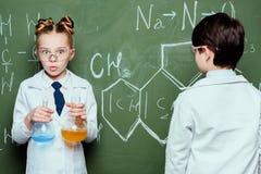 Pojke och flicka i vitlag som står med agens i flaskor och drar kemiska formler Arkivbild