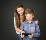 Pojke och flicka med den digitala minnestavlan. Intresserat i teknologi Arkivbilder
