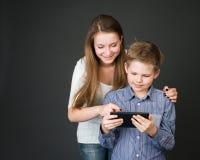 Pojke och flicka med den digitala minnestavlan. Intresserat i teknologi Arkivfoton