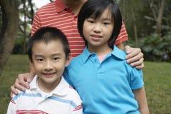 Pojke och flicka med fadern In Park arkivfoto