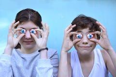 Pojke och flicka med jujubemarshmellowögon som ler öppet munslut upp ståenden arkivbild