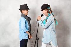 Pojke och flicka med mikrofonen arkivfoton