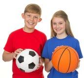 Pojke och flicka med sportbollar Arkivbilder