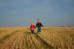 Pojke och flicka på fältet Arkivfoto