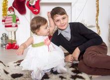 Pojke och flicka runt om en julspis Fotografering för Bildbyråer