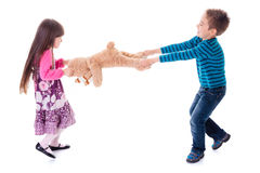 Pojke och flicka som drar leksakbjörnen Arkivbild