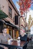 Pojke och flicka som dricker kaffe och att le royaltyfri foto
