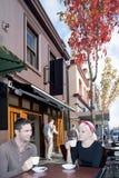 Pojke och flicka som dricker kaffe nära restaurang arkivbilder